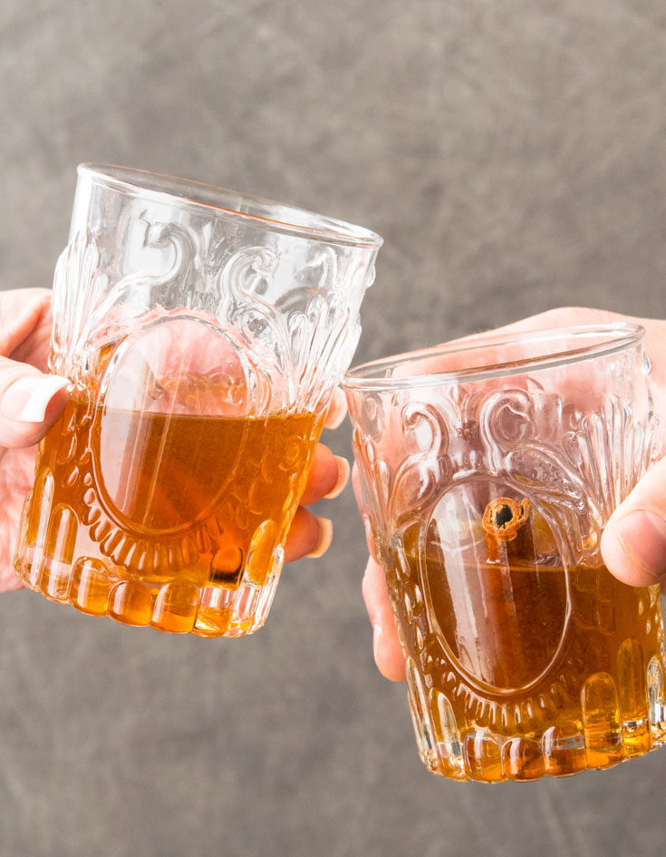 Two people toasting with glasses of Apple Pie Moonshine