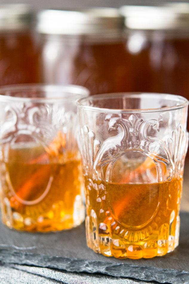 Two glasses of Apple Pie Moonshine with cinnamon sticks