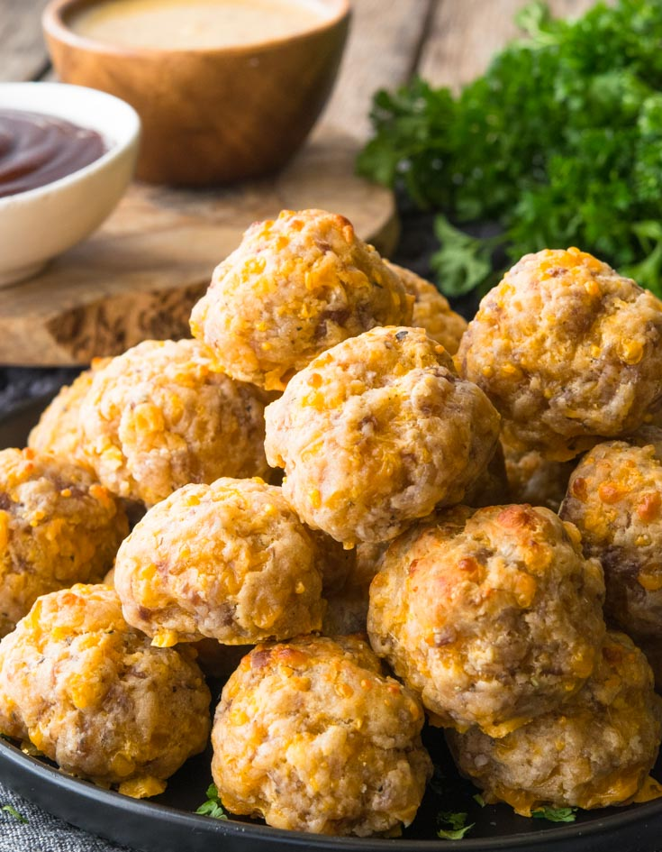 A pile of Bisquick Sausage Balls on a plate with dipping sauces on the side