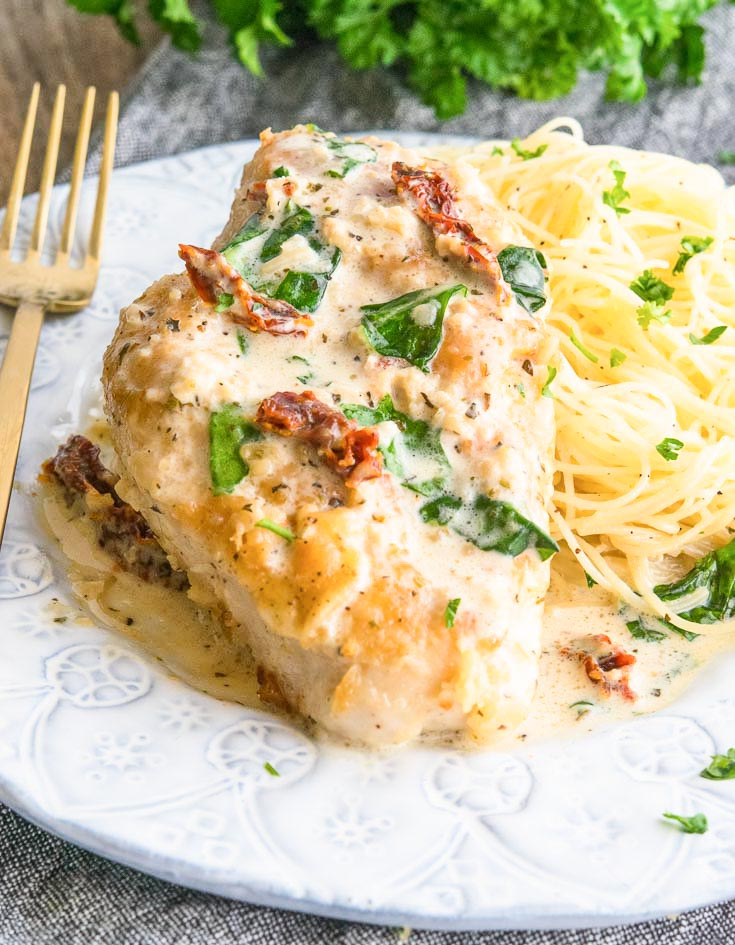 Creamy Tuscan Garlic Chicken on top of pasta, on a plate with fork on the side