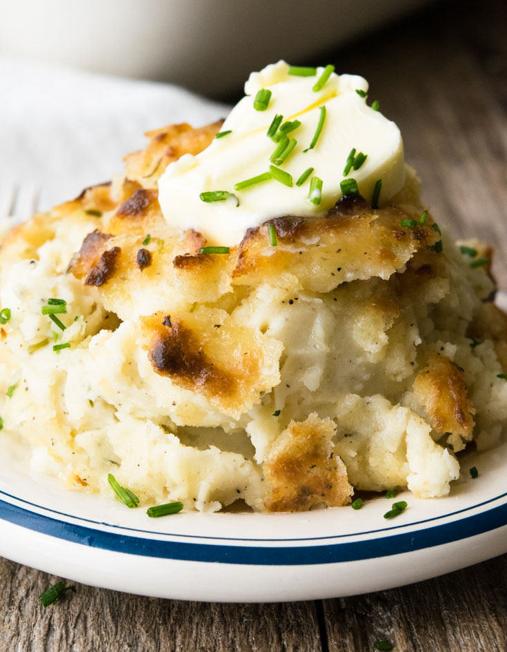 Make Ahead Mashed Potatoes topped with a slice of butter and chopped chive on a plate