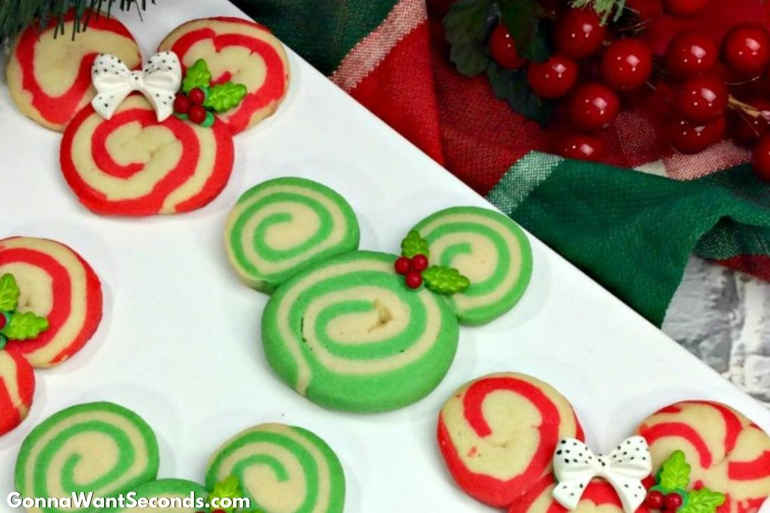 Mickey and Minnie Swirl Cookies on a serving plate with Christmas decor on the side