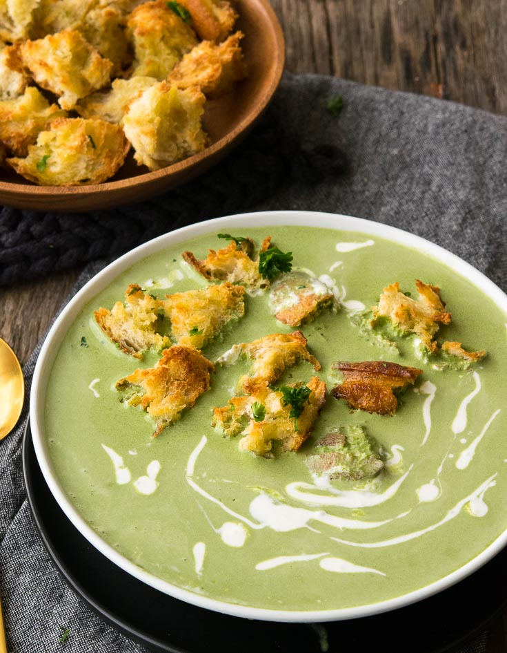 Spinach Soup with croutons and drizzle of heavy cream on top, in a white bowl