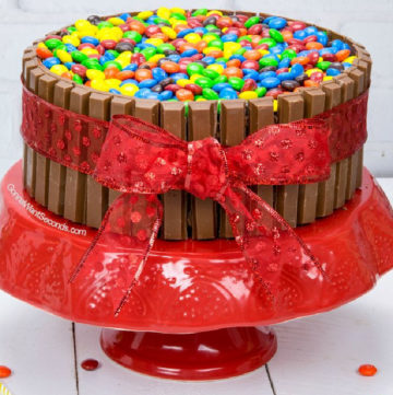 Kit Kat Cake tied around with a red ribbon with M&Ms on top, on a red cake stand