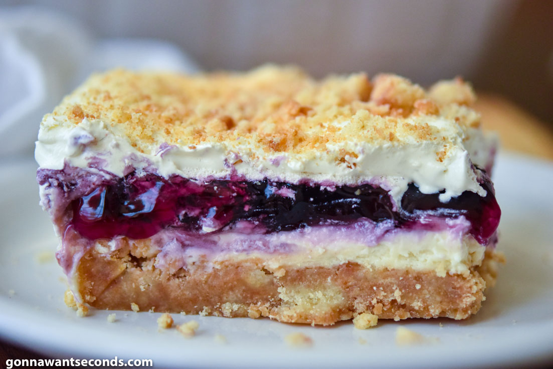 A slice of Blueberry Yum Yum, showing layers of cream cheese and blueberries