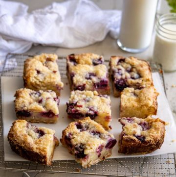 Cherry Custard Pie Bars on a cooling rack, with a glass of milk on the side