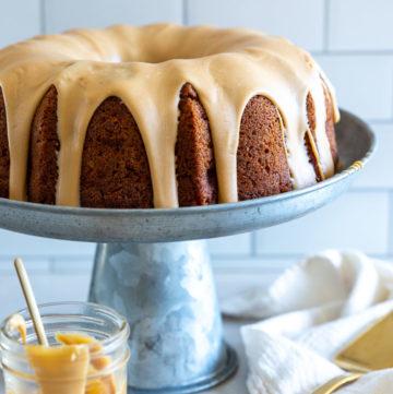 Apple Bundt Cake with brown sugar glaze on a metal cake stand