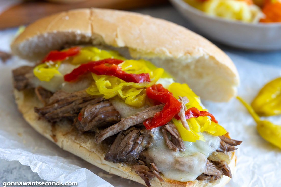 crockpot Italian beef sandwiches, topped with pepperoncini and extra Giardiniera, close up