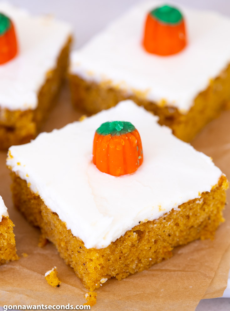 Slices of Pumpkin Bars with Cream Cheese Frosting, decorated with candy pumpkin