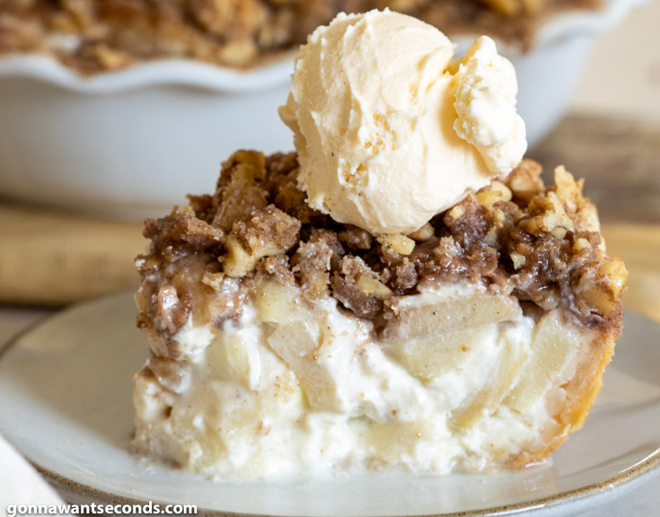 A slice of sour cream apple pie filling with crumb topping and a scoop of vanilla ice cream on top
