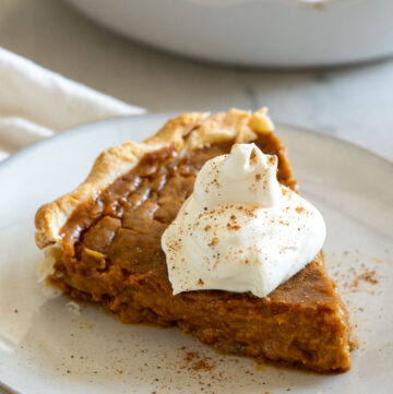 A slice of pumpkin pie topped with a dollop of whipped cream