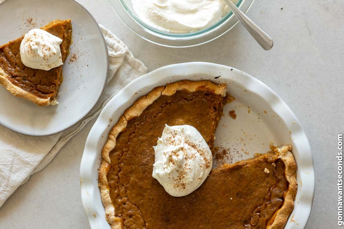 Whole pumpkin pie with canned pumpkin with a slice cut out on a small plate