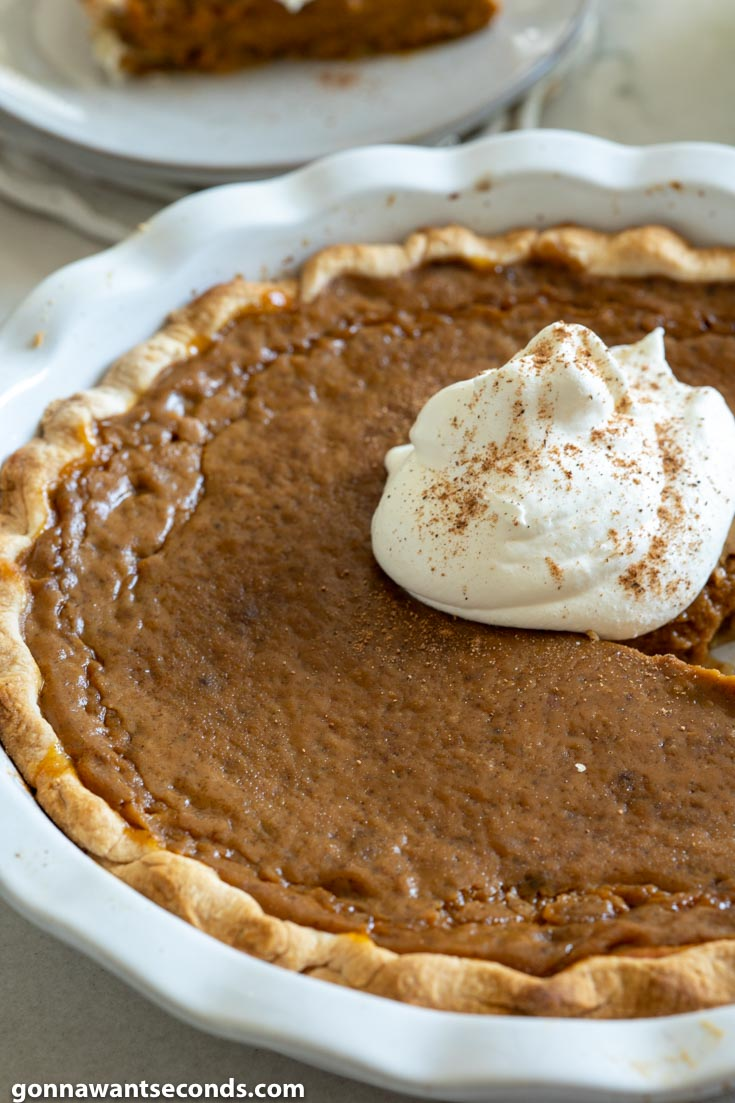 Whole easy pumpkin pie recipe with a dollop of whipped cream