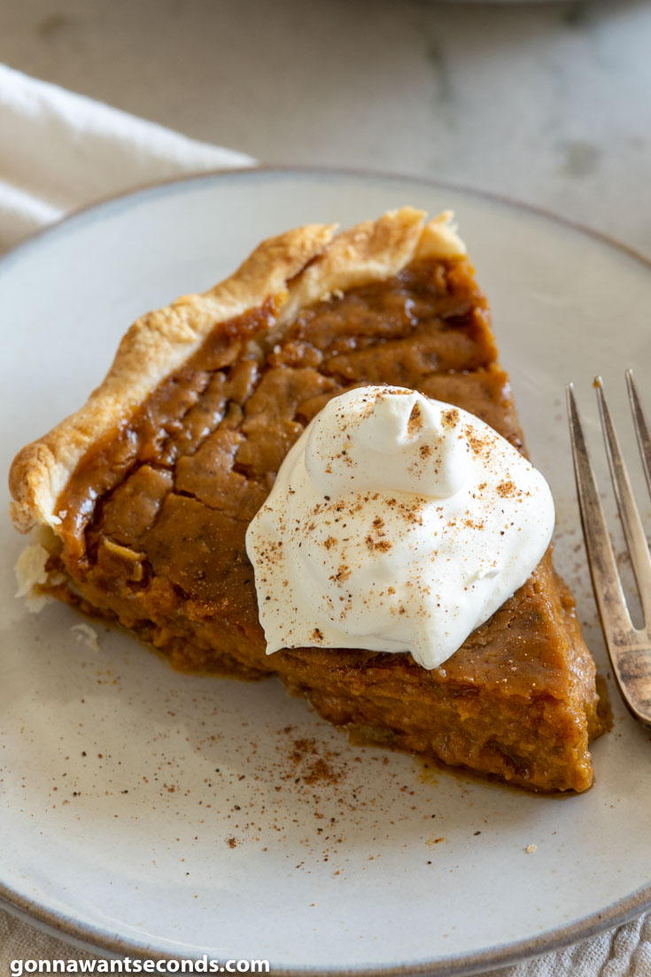 A slice of homemade pumpkin pie recipe with a dollop of whipped cream