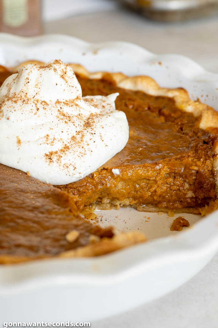 Whole pumpkin pie with a slice cut out, topped with a dollop of whipped cream