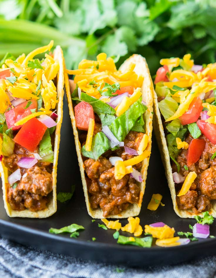 Taco Meat Recipe in taco shells, topped with chopped tomatoes, cheese, onions, and lettuce.